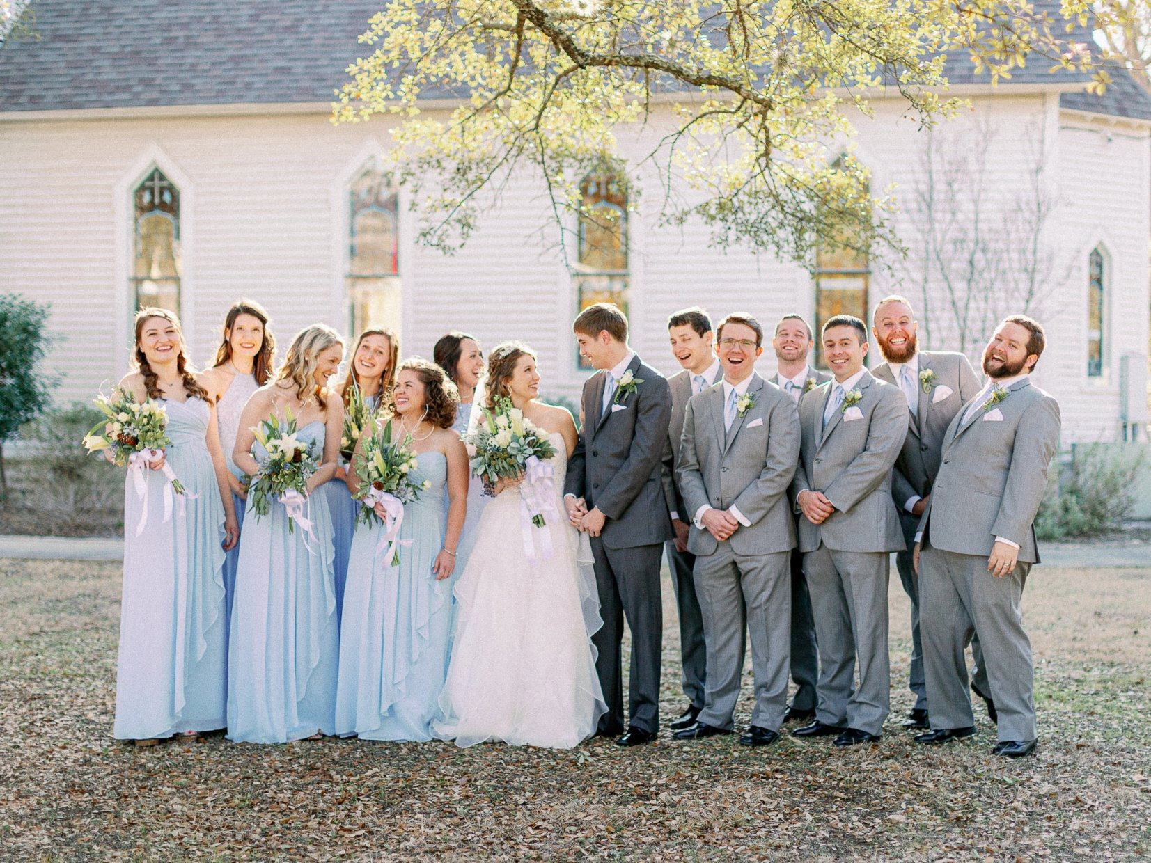 Laughing photo of wedding party wearing pastel blue colors in front of a church