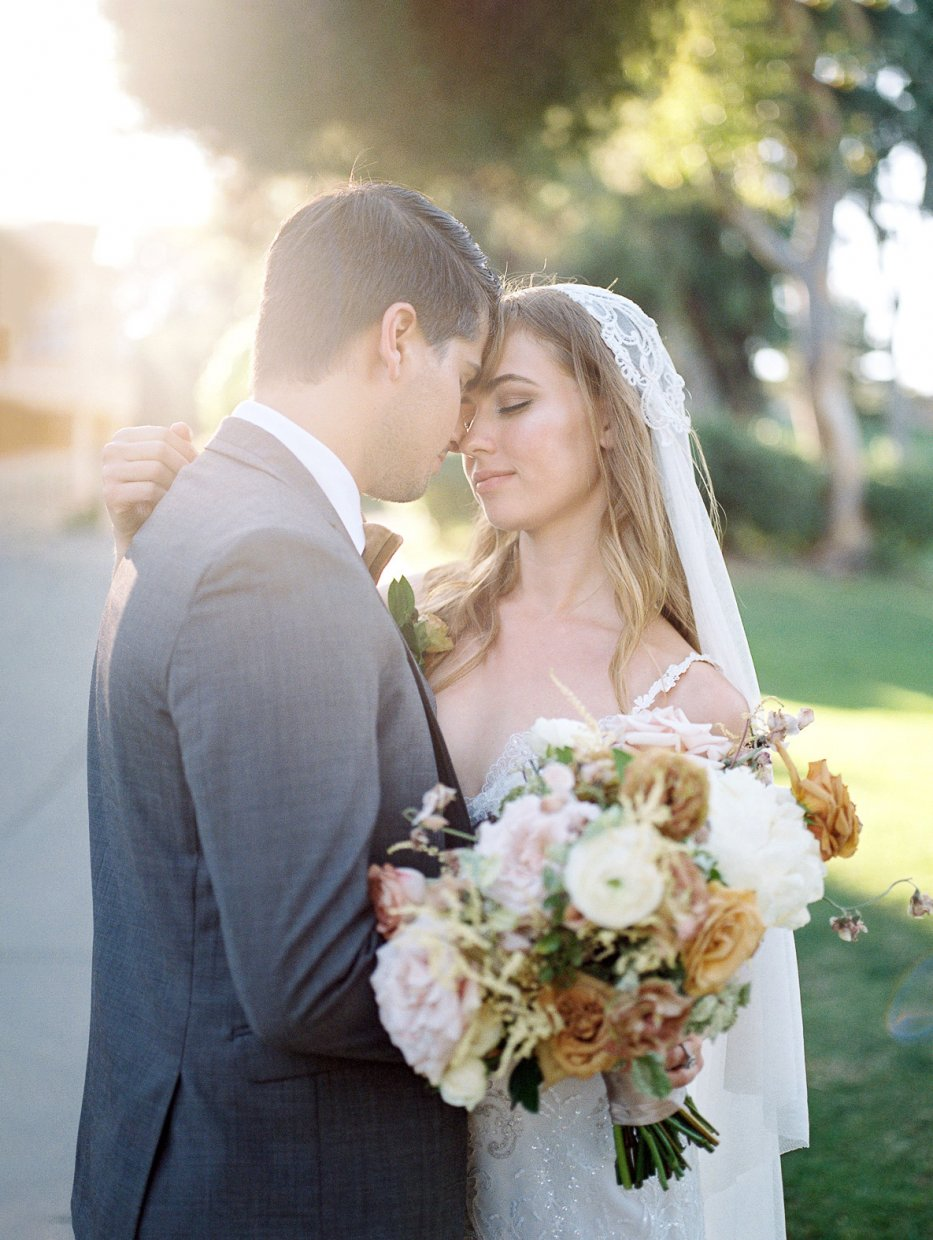 Romantic hazy wedding photo of couple touching foreheads, and bride is holding a bouquet at Marbella Country Club in San Juan Capistrano.